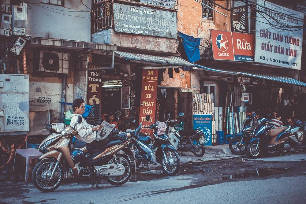 Mann mit Zeitung auf Motorrad in Vietnam