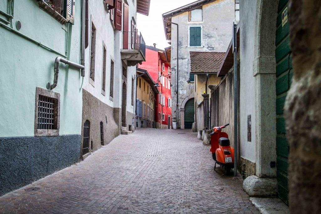 orangefarbener Roller in einer Seitenstraße von Arco