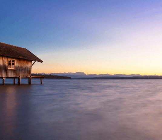 Bootshaus und Berge im Hintergrund bei Sonnenuntergang